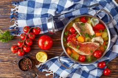 Hearty fish soup in a pot. Hearty fish soup - greek psarosoupa in a metal casserole on an old rustic table with ladle, tomatoes, peppercorns and kitchen towel royalty free stock photo