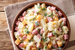 Hearty Hawaiian salad with pasta, ham, pineapple, onion, cheddar. Cheese dressed with mayonnaise close-up in a bowl on the table. horizontal top view from above Royalty Free Stock Images