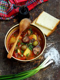 Hearty homemade soup with potatoes, carrots, sausages and olives in a clay bowl on a wooden background. Stock Photography