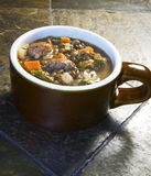 Hearty Lentil, Escarole and Italian Sausage Soup. Crock of hearty italian sausage and lentil soup on slate table royalty free stock photos