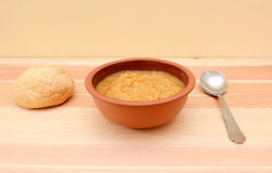 Hearty lentil soup served with a crusty bread roll Stock Photo