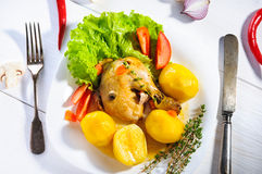 Hearty lunch or dinner: plate of ckicken leg and potatoes with green leaf lettuce, red tomatoes on white table surface, top view. Hearty lunch or dinner: plate Stock Photography