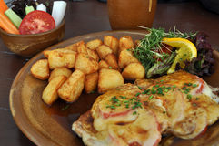 Hearty Meal. Meat topped with melted cheese, fried potatoes, salad and cucumber. tomatoes and carrots stock photos