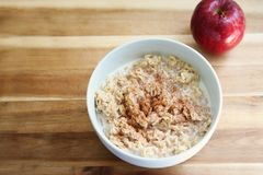 Hearty Oatmeal Breakfast. Hearty Warm Bowl of Oatmeal Topped with Cinnamon and Milk. The addition of an apple really completes this healthy meal stock photos