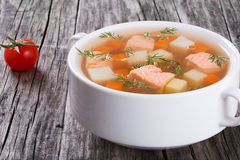 Hearty salmon chowder on white bowl with dill Stock Images