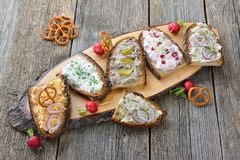 Snack with spreads. Hearty snack with different kinds of spreads on farmhouse bread served on an old wooden table Royalty Free Stock Images