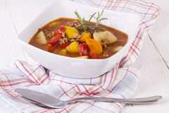 Hearty Stew in Bowl and Spoon on Plaid Dish Towel Royalty Free Stock Image