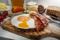 Hearty supper, fried egg and bacon on protein bread Royalty Free Stock Images