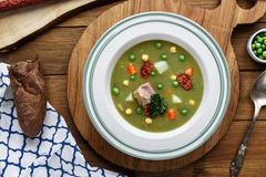 Hearty traditional Dutch pea soup with smoked sausage, rye bread and bacon. Or: `erwtensoep met rookworst, roggebrood en Royalty Free Stock Images