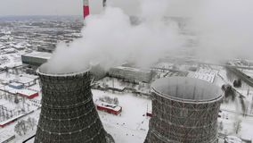 Heat electric station in winter. Aerial view. Top view, copter shoot. Thermal power in winter. Residential heat supply. Flying over the large pipes of the stock video footage