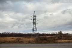 Heat haze rises as powerlines blur into the distance. High voltage power line and asphalt road Royalty Free Stock Photo
