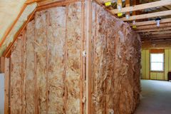 Heat insulation and wooden logs lathing ready for Finishing made of tongue and groove planks. Stock Photos