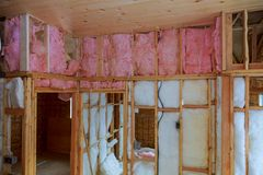 Heat isolation in a new house with mineral wool, home wood. Heat isolation in a new house with mineral wool, wood home insulation fiberglass glasswool royalty free stock photography