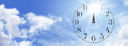 Heat of the midday sun. Wide blue sky and fluffy clouds banner with a transparent clock face showing midday and a bright sunburst behind the 12 Royalty Free Stock Photos