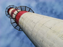 Heat plant chimney. Against blue sky and clouds, frog view royalty free stock photography