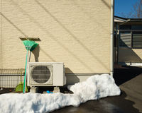 Heat pump unit on the side of a home in winter. Royalty Free Stock Images
