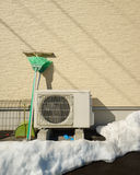Heat pump unit on the side of a home in winter. Stock Photography