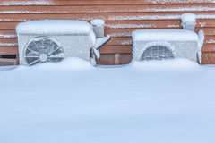 Heat Pumps. Two residential heat pumps buried in snow Royalty Free Stock Photo