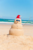Heat Resistent Snowman Sunbathing On Beach. Snowman made out of sand with ocean in background. Sandman is wearing Sunglasses and santa hat could be used for Royalty Free Stock Photo