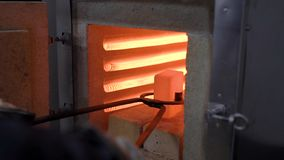 Heat treatment shop. Hot metal part in special tongs