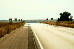 Heat Wave. A long rural road glistens with a mirage of water in the summer heat stock photography