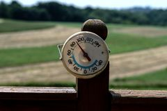 Heat wave in Appalachia. Thermometer reading 90 degrees Fahrenheit with out of focus corn and hay fields in the background in rural Appalachia stock photography