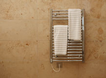 Heated Bathroom Towel Rail. Modern heated towel rail on tiled bathroom wall royalty free stock photography