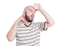 Heated man cooling down with cold water plastic bottles Royalty Free Stock Images