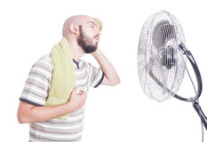 Heated man wiping sweat in front of cooler Stock Photos