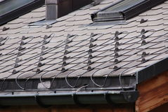 Heated roof tiles in Switzerland. In the Swiss ski resort of Leukerbad all the roofs of the ski chalets have a heating system on the end of the roof to melt the Royalty Free Stock Images