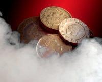 Heated UK economy. UK coins on red background overlaid with smoke effect Stock Images