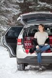 Heated up young Caucasian woman in unbutton fur coat sits in trunk of own car. Resting and breathing in winter forest Royalty Free Stock Photo