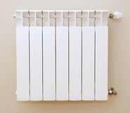 Heater. A white heater hangs on a background a beige wall Royalty Free Stock Image