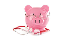 Heath care. Piggy bank wearing glasses with stethoscope in the studio Stock Photos