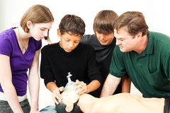 Heath Education - Oxygen Mask CPR. Teenage students and their teacher, using an oxygen mask on a CPR dummy Royalty Free Stock Photos