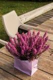 Heather dans un sac rose a placé sur la table rustique en bois images stock