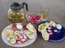 Heathy breakfast or snack, close up plates with bread with slice. D radish and boiled eggs, ham and cheese with green tea pot and glass on brown wooden table Stock Photography