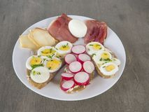 Heathy breakfast or snack, close up white plate with bread with. Sliced radish and boiled eggs with chive, ham and cheese on brown wooden table, top view Royalty Free Stock Photos
