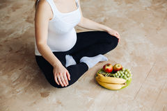 Heathy food for my baby. Pregnant woman holding a plate with fruits. Nutritional needs during pregnancy found in milk. Heathy food for my baby. Pregnant woman Stock Photo