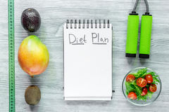 Heathy food for slimming. Notebook for diet plan, fruits and measuring tape on grey wooden table top view mock up.  Stock Images
