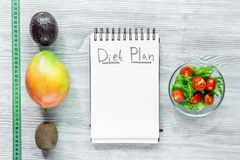 Heathy food for slimming. Notebook for diet plan, fruits and measuring tape on grey wooden table top view mock up.  Royalty Free Stock Images