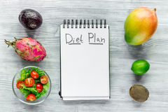 Heathy food for slimming. Notebook for diet plan, fruits and salad on grey wooden table top view mock up.  Stock Images