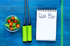 Heathy food for slimming. Notebook for diet plan, salad and measuring tape on blue wooden table top view mock up. Heathy food for slimming. Notebook for diet Royalty Free Stock Photo