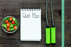 Heathy food for slimming. Notebook for diet plan, salad and measuring tape on wooden table top view mock up.  Stock Photos