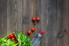 Heathy meal in office. Lunch box with tomato and salad on dark wooden background top view copyspace. Heathy meal in office. Lunch box on dark wooden table Stock Photography