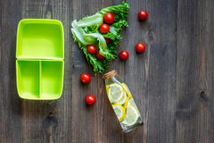 Heathy meal in office. Lunch box with tomato and salad on dark wooden background top view copyspace. Heathy meal in office. Lunch box on dark wooden table Royalty Free Stock Photo