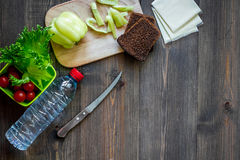 Heathy meal in office. Lunch box with vegetables, cheese and bread on dark wooden background top view copyspace. Heathy meal in office. Lunch box on dark wooden Royalty Free Stock Photo
