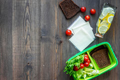 Heathy meal in office. Lunch box with vegetables, cheese and bread on dark wooden background top view copyspace. Heathy meal in office. Lunch box on dark wooden Stock Image