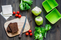 Heathy meal in office. Lunch box with vegetables, cheese and bread on dark wooden background top view. Heathy meal in office. Lunch box on dark wooden table Stock Image