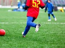 Heathy pojke för ung aktiv sport i den röda och blåa sportswearen som kör och sparkar en röd boll på fotbollfält royaltyfria foton